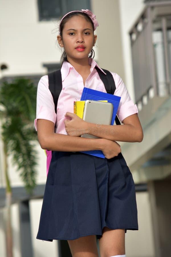 Ernstes junges Minderheits-Schulmädchen mit dem Buch-Gehen lizenzfreies stockbild