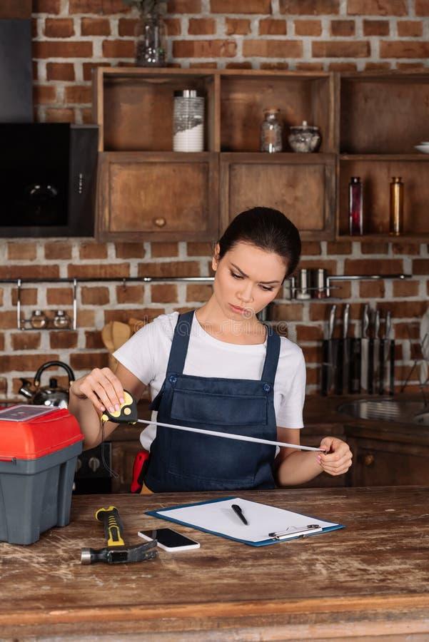 ernstes junges repairwoman mit messendem Band und Klemmbrett stockfotografie
