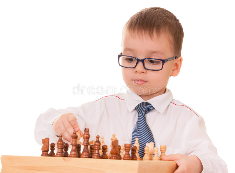 Ernstes Kind, das Schach spielt stockfotos
