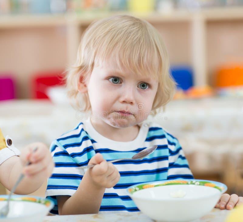 Ernstes Kind, das von den Platten im Kindergarten isst stockbild