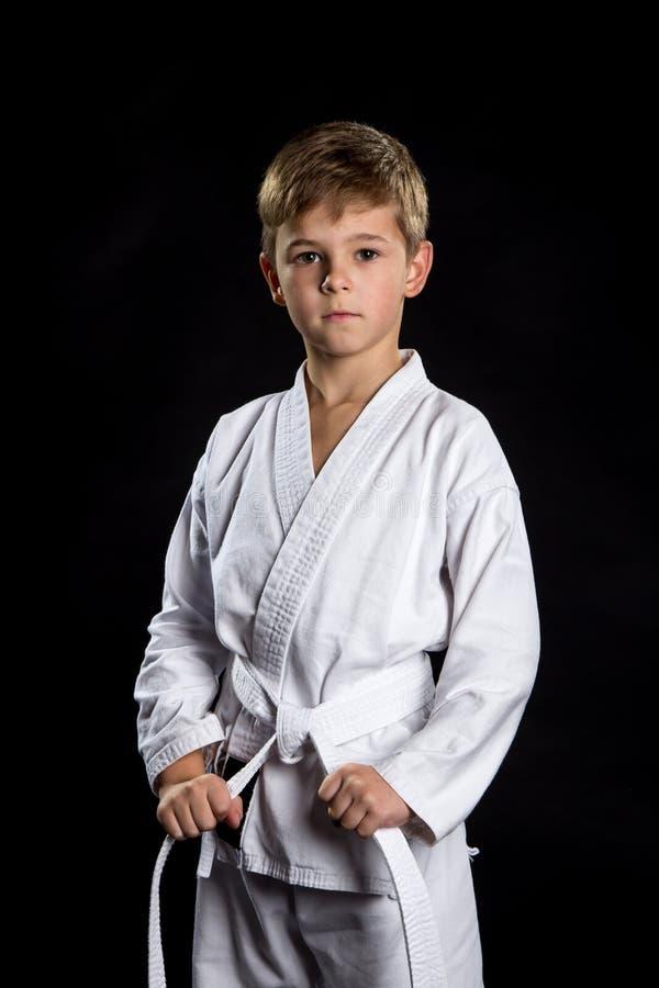 Ernstes Kind im nagelneuen Kimono in der vorderen Position auf dem schwarzen Hintergrund Karatekämpfer, der seinen Gurt hält lizenzfreies stockfoto