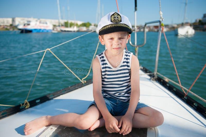 Ernstes Kind in Kapitänhut, der auf Luxusyachtbrett im Seehafen im Sommer sitzt stockbild