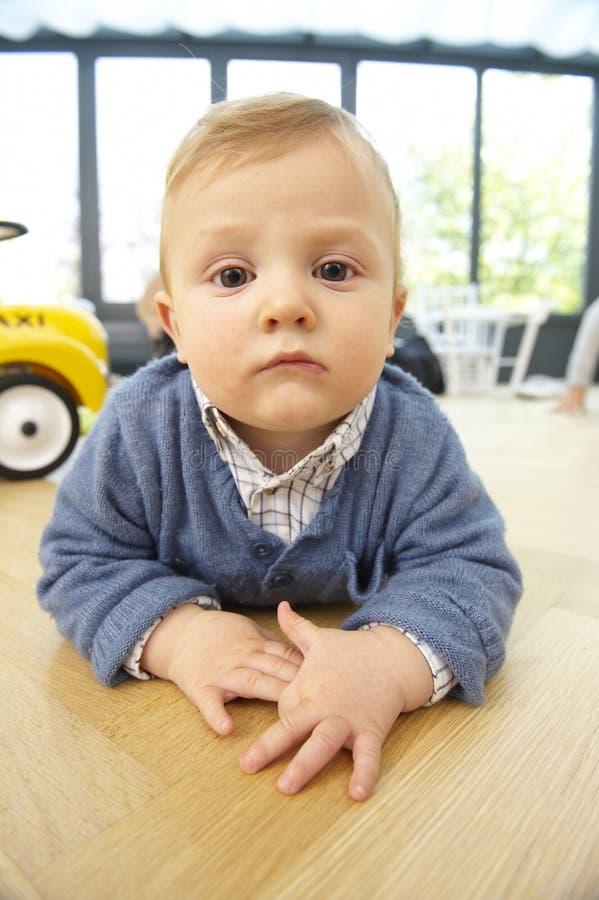 Ernstes Kleinkind, das auf dem Fußboden liegt stockbild