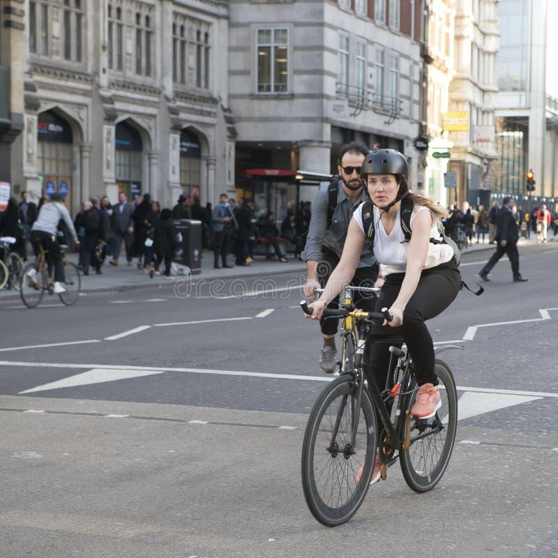 ernstes Mädchen in einem blauen Kleid mit den Tupfen, welche die Straße auf einem Fahrrad kreuzen lizenzfreie stockfotos