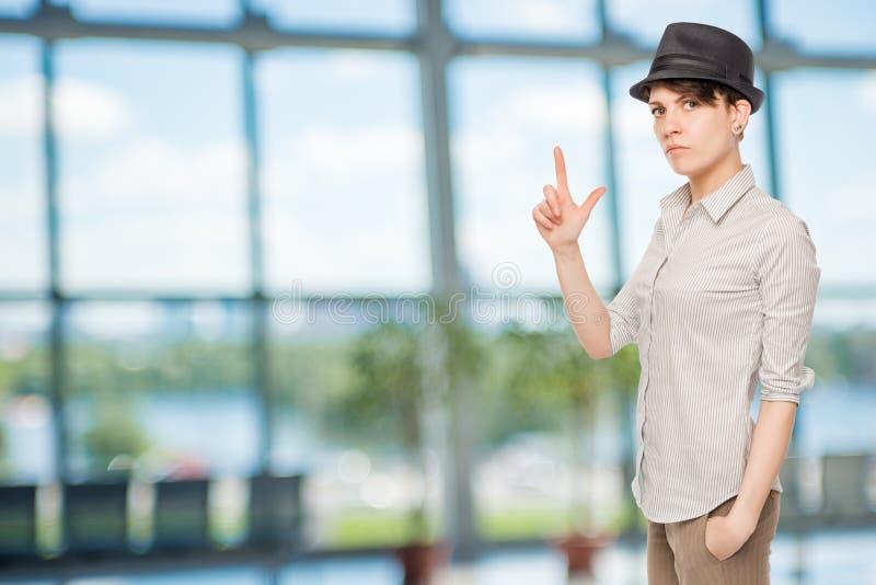Ernstes Mädchen hält Fingerpistole und trägt einen schwarzen Hut lizenzfreies stockbild
