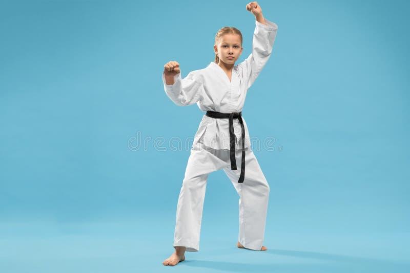 Ernstes Mädchen im Kimono, der Karate auf blauem Hintergrund tut stockfotografie
