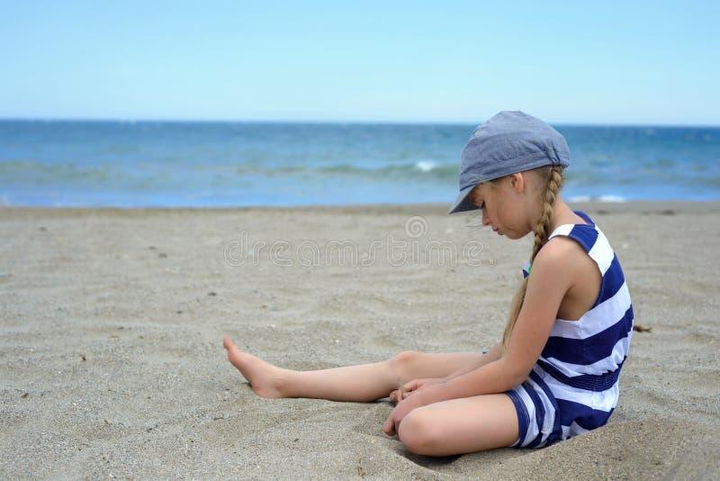 Ernstes nettes kleines Mädchen, das auf dem Strand sitzt stockfotos