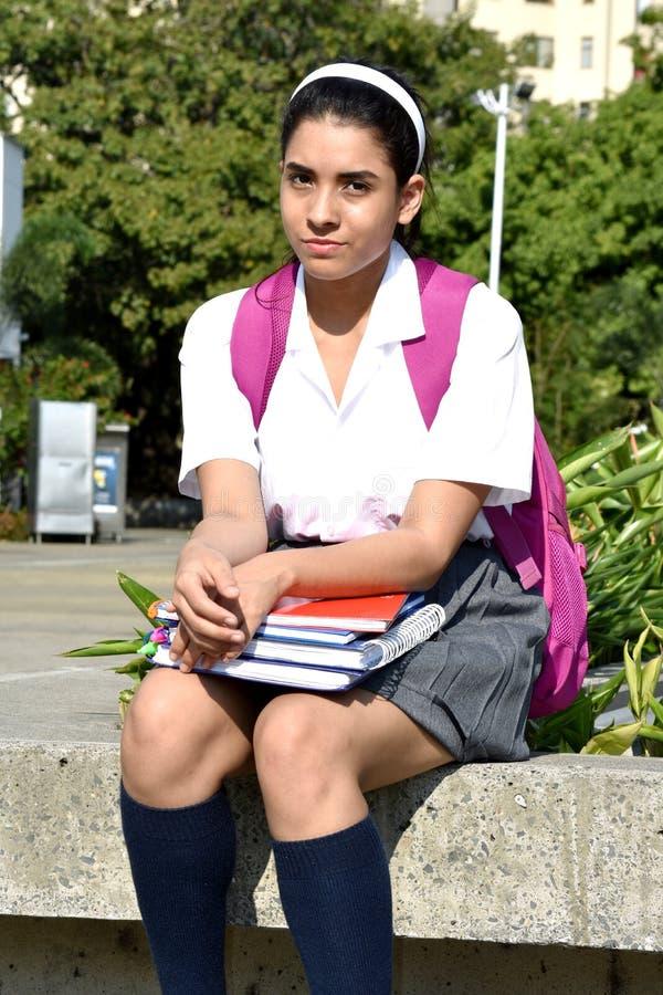 Ernstes nettes kolumbianisches Schulmädchen-tragendes Schuluniform-Sitzen lizenzfreies stockfoto