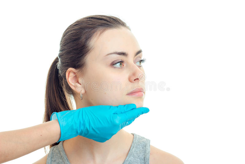 Ernstes Porträt eines jungen Mädchens, das zum Kosmetiker kam und er betrachtet ihr Gesicht in einer blauen Handschuhnahaufnahme stockbilder