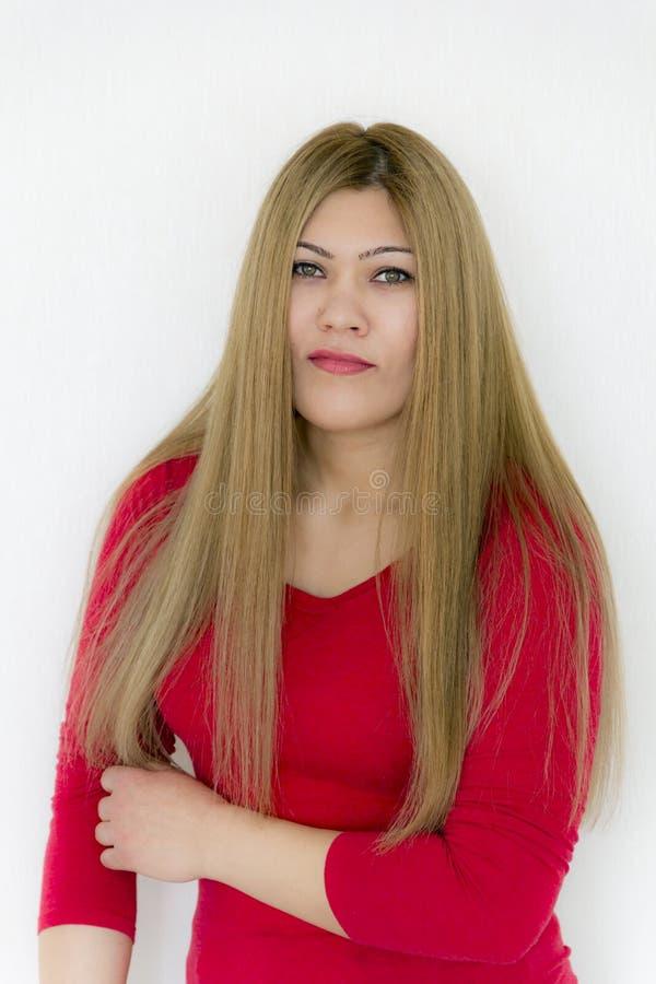 Ernsthaft Mädchen mit dem langen braunen gesunden geraden Haar im Rot stockfotografie