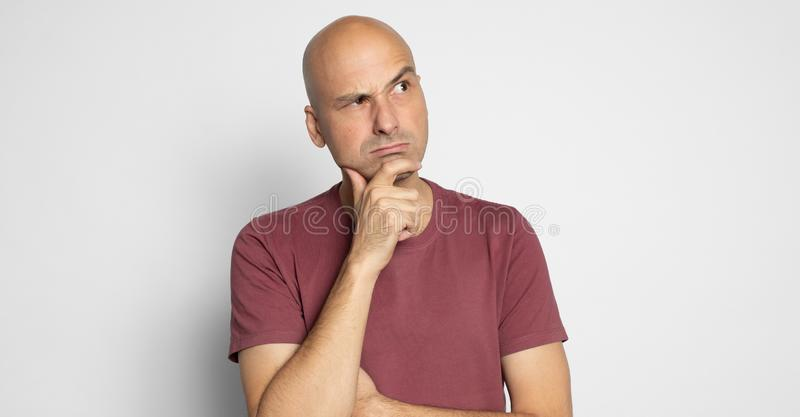 Ernsthafte Glatze denkt nach oben, um Platz vereinzelt zu kopieren lizenzfreie stockfotografie