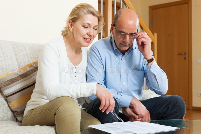 Ernstig bejaard paar met financiële documenten stock foto