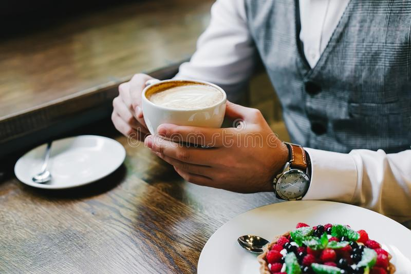 Ernstig bemant handen houdend een kop van hete cappuccino royalty-vrije stock foto's