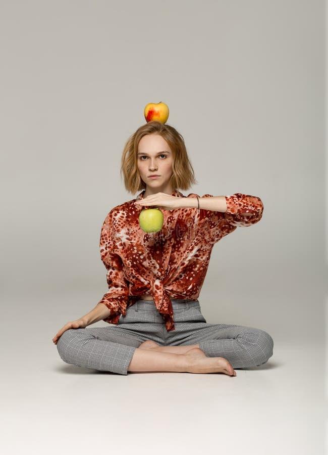 Ernstig blondemeisje in in rode overhemdszitting in yogapositie stock foto's