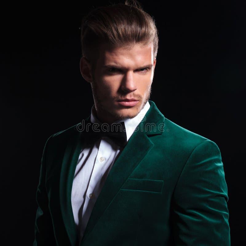 Ernstig gezicht van een jonge mens die groen fluweelkostuum dragen stock afbeelding