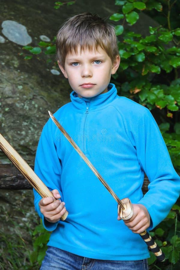 Ernstig jong geitje met een houten zwaard op steen royalty-vrije stock fotografie