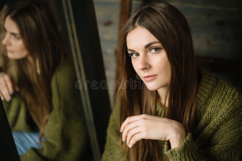 Ernstig jong meisje in donkergroene gebreide comfortabele sweaterzitting op de vloer De gelukkige jonge zakken van de meisjeshold royalty-vrije stock foto's