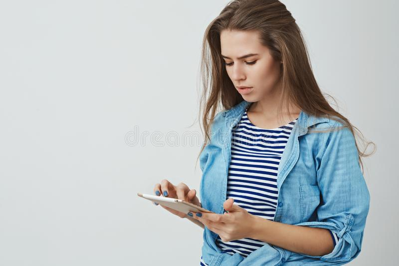 Ernstig-kijkend modern modieus jong modieus Europees meisje die het digitale tablet het typen dringende vertoning kijken houden stock fotografie