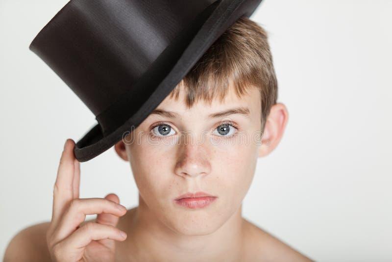 Ernstig kind die zijn hoed op hoofd tippen royalty-vrije stock foto's