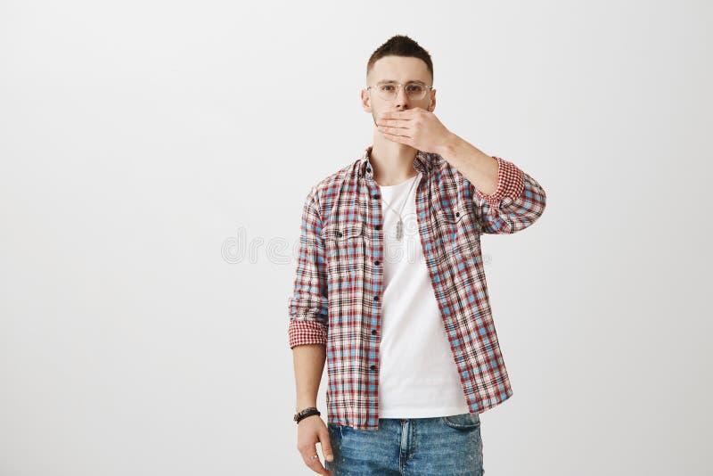 Ernstig knap mannelijk model in glazen en in gecontroleerd overhemd die mond behandelen met palm en bij camera over staren royalty-vrije stock fotografie