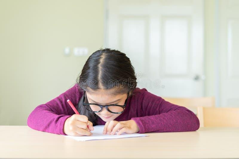 Ernstig meisje die op een document in klaslokaal schrijven stock foto