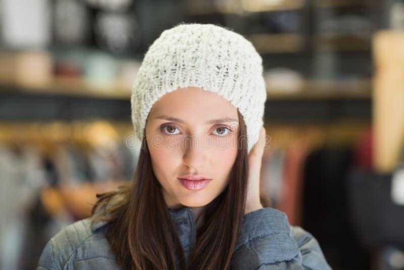 Ernstig mooi brunette die camera met de winterkleren bekijken stock afbeelding