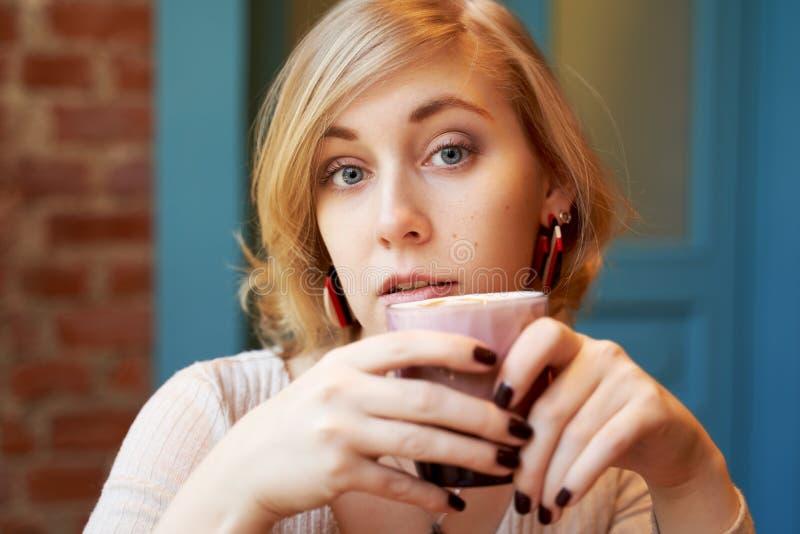 Ernstig nadenkend meisje die de camera bekijken Een jonge vrouw het drinken koffie in een koffie tegen een bakstenen muur en een  stock foto's