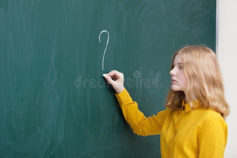 Ernstig schoolmeisje bij het bord met vraagteken royalty-vrije stock fotografie