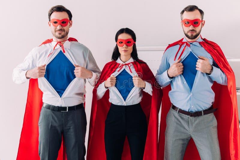 ernstig super zakenlui in maskers en kaap die blauwe overhemden tonen royalty-vrije stock fotografie