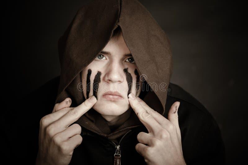Ernstig teenaged de verf van jongensvlekken op zijn gezicht royalty-vrije stock afbeeldingen