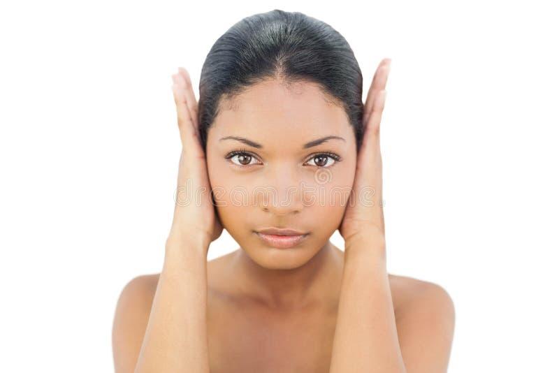 Ernstig zwart haired model die haar oren blokkeren stock afbeelding