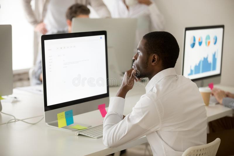 Ernstige Afrikaans-Amerikaanse werknemer die over zaken e-mail w denken stock fotografie