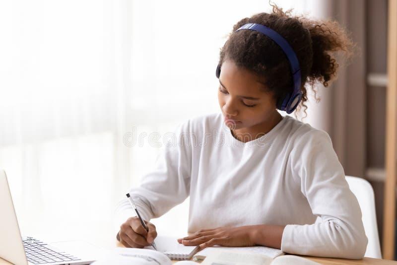 Ernstige Afrikaanse Amerikaanse tiener die hoofdtelefoons draagt, die thuiswerk doen royalty-vrije stock foto