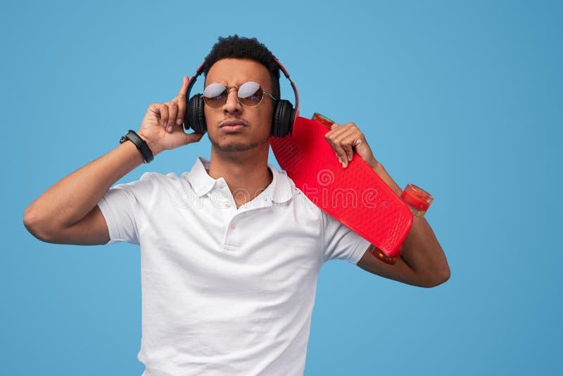 Ernstige Afrikaanse hipster die aan muziek luisteren stock foto's