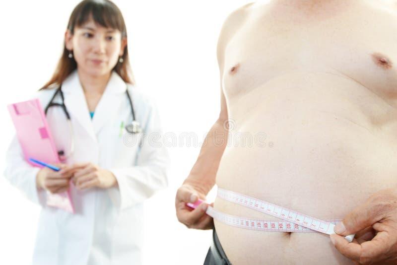 Ernstige arts die een geduldige zwaarlijvigheid onderzoeken royalty-vrije stock foto
