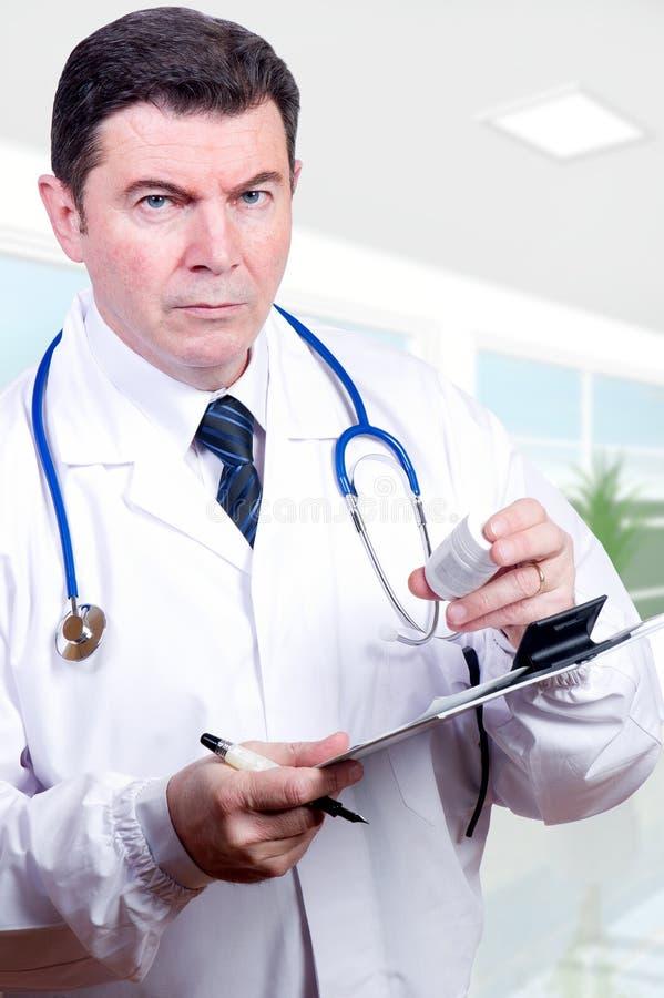 Ernstige arts met pillen stock afbeelding