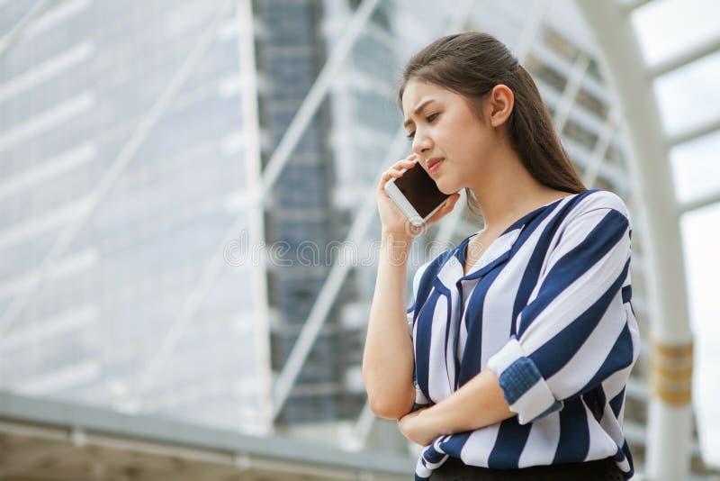 Ernstige Aziatische jonge bedrijfsvrouw die op mobiele telefoon in stedelijke stad spreken royalty-vrije stock fotografie