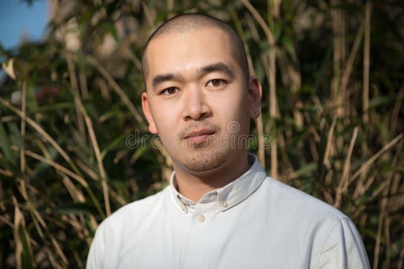 Ernstige Aziatische mens die camera tegen rietachtergrond bekijken stock afbeeldingen