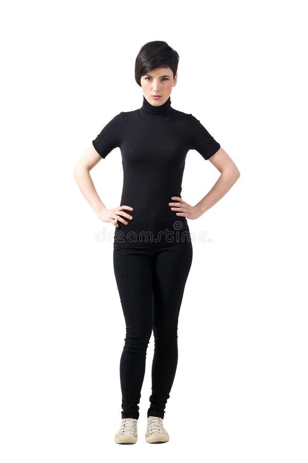 Ernstige bazige korte haar mooie vrouw met handen op heupen stock foto's