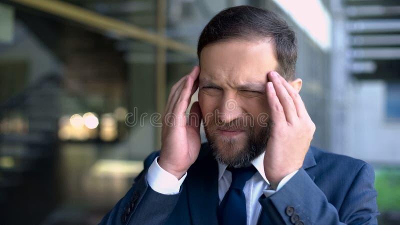 Ernstige bedrijfsmens die aan migraine, hoofdpijnwanorde, symptomen lijden royalty-vrije stock afbeelding