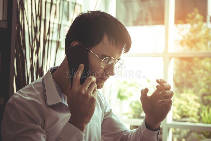 Ernstige Bedrijfsmens die vraag op zijn mobiele telefoon maken stock afbeelding