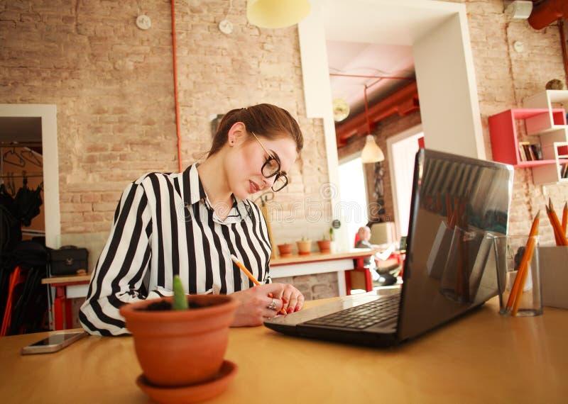 Ernstige bedrijfsvrouw die bij bureau met laptop in bureau schrijven stock afbeelding