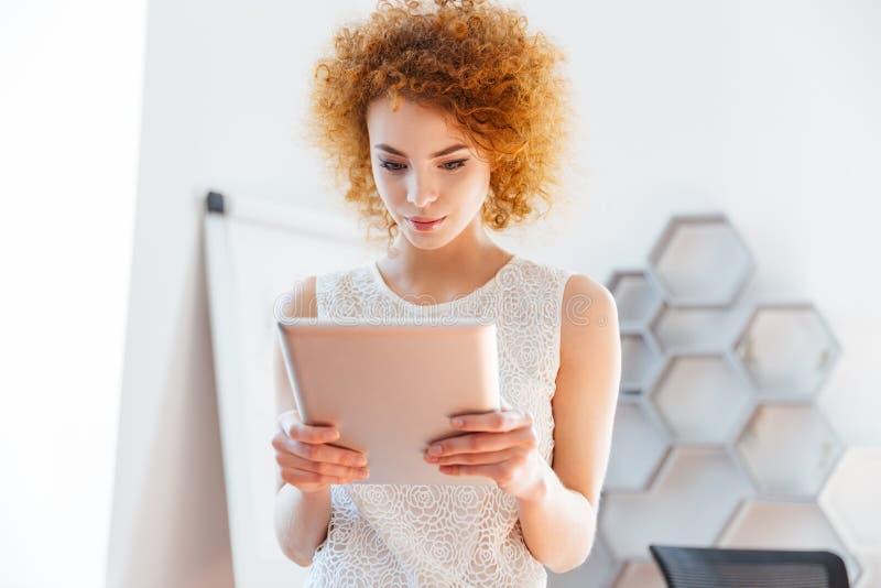 Ernstige bedrijfsvrouw die tablet in bureau gebruiken stock afbeelding