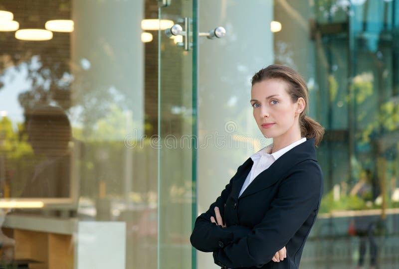 Ernstige bedrijfsvrouw die zich buiten met gekruiste wapens bevinden stock foto