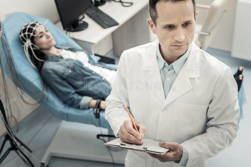 Ernstige bekwame arts die in een potlood een gat maken stock foto's