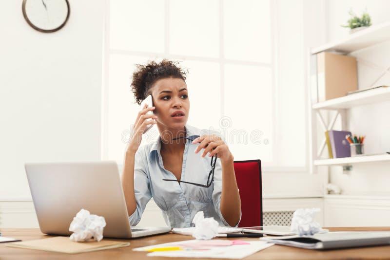 Ernstige boze bedrijfsvrouw aan het werk die op telefoon spreken royalty-vrije stock foto's