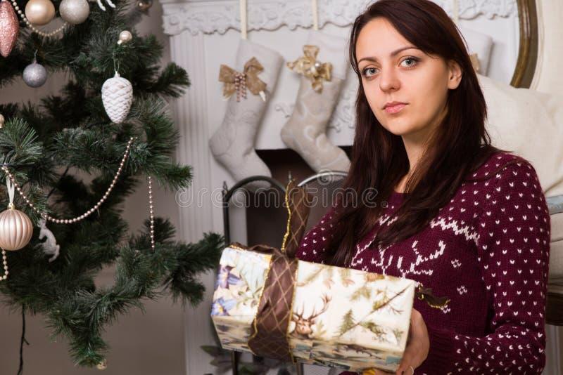Ernstige de Giftdoos van de Vrouwenholding dichtbij Kerstboom stock afbeelding