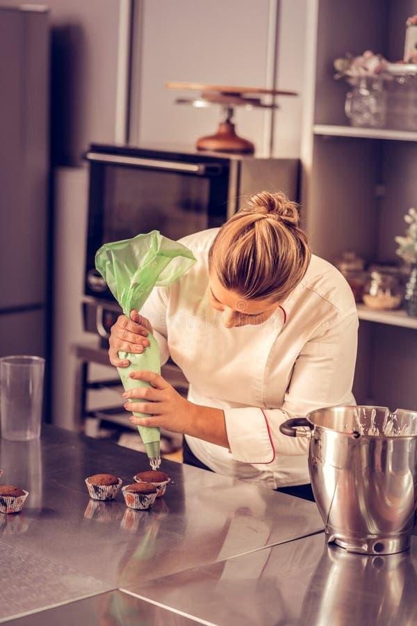 Ernstige deskundige gebakjechef-kok die een leidingenzak met behulp van stock fotografie