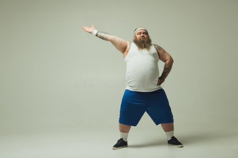Ernstige dikke kerel in sportkleding die zijdelings richten stock fotografie