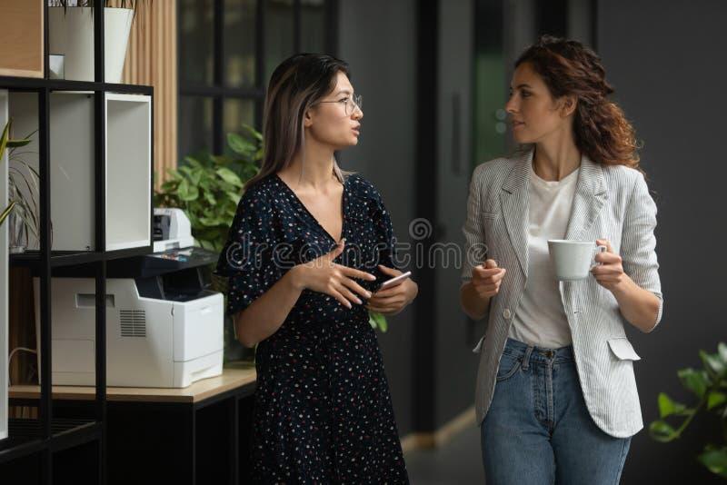 Ernstige diverse vrouwelijke collega's die praten in kantoorruimte stock foto's